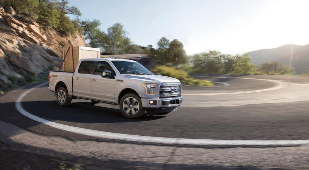 A white 2015 Ford F-150 is hauling a crate around a corner.