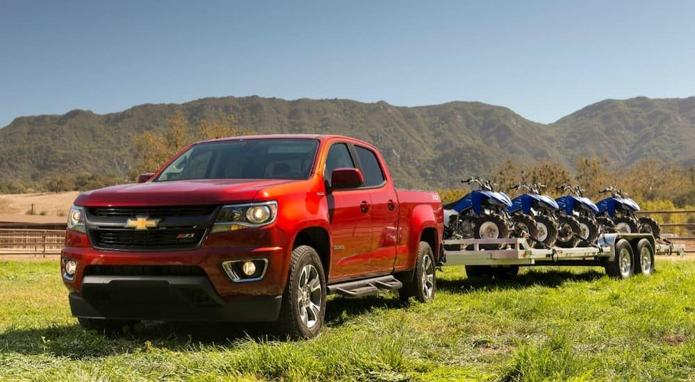 A red 2018 Chevy Colorado has four-wheelers on a trailer while on grass in front of mountains.