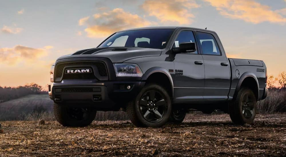 A grey 2019 Ram 1500 Classic, which is popular among used trucks for sale, is parked off-road at sunset in Lexington, KY.