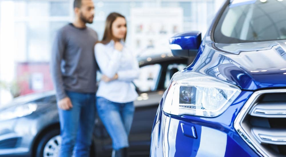 An out of focus couple is looking at used vehicles for sale in a showroom.