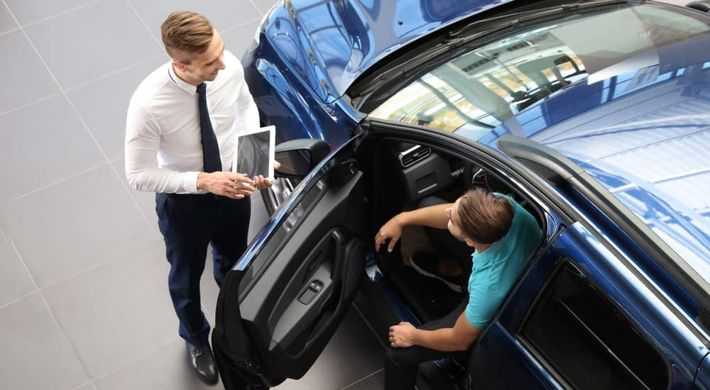 A customer is sitting in a blue car while talking to a salesman, shown from above.