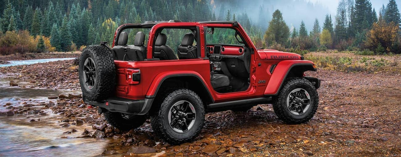 A red 2020 Jeep Wrangler is parked on a rocky river bank near Lexington, KY.