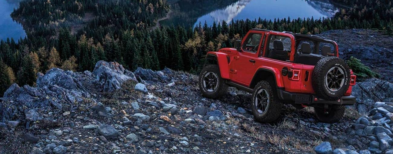 A red 2020 Jeep Wrangler is overlooking lakes from a rocky ledge.