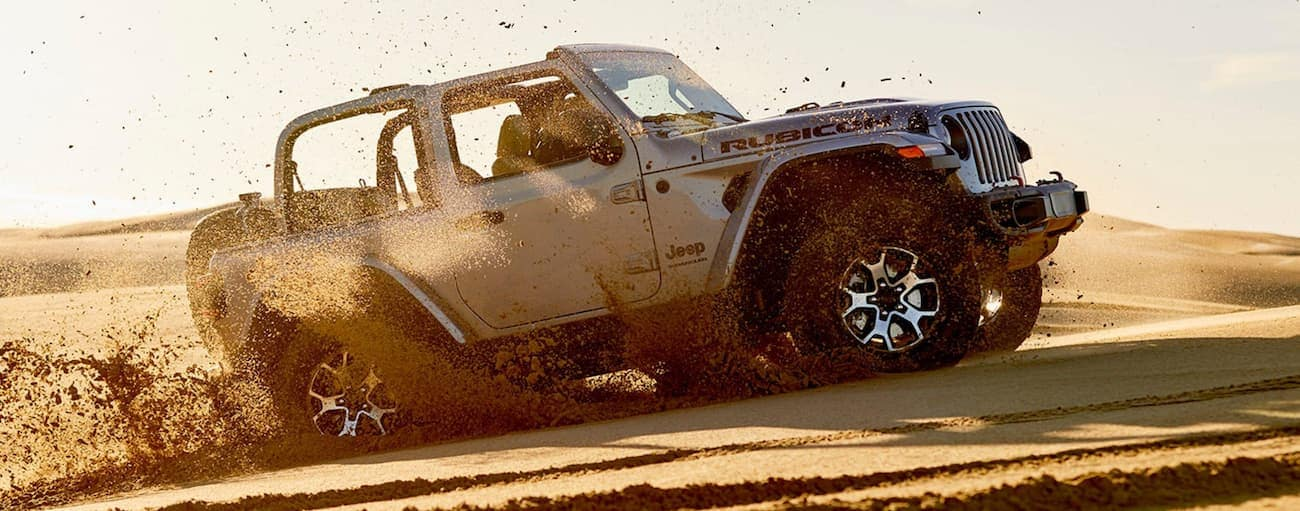 A silver 2020 Jeep Wrangler is driving on a sand dune.