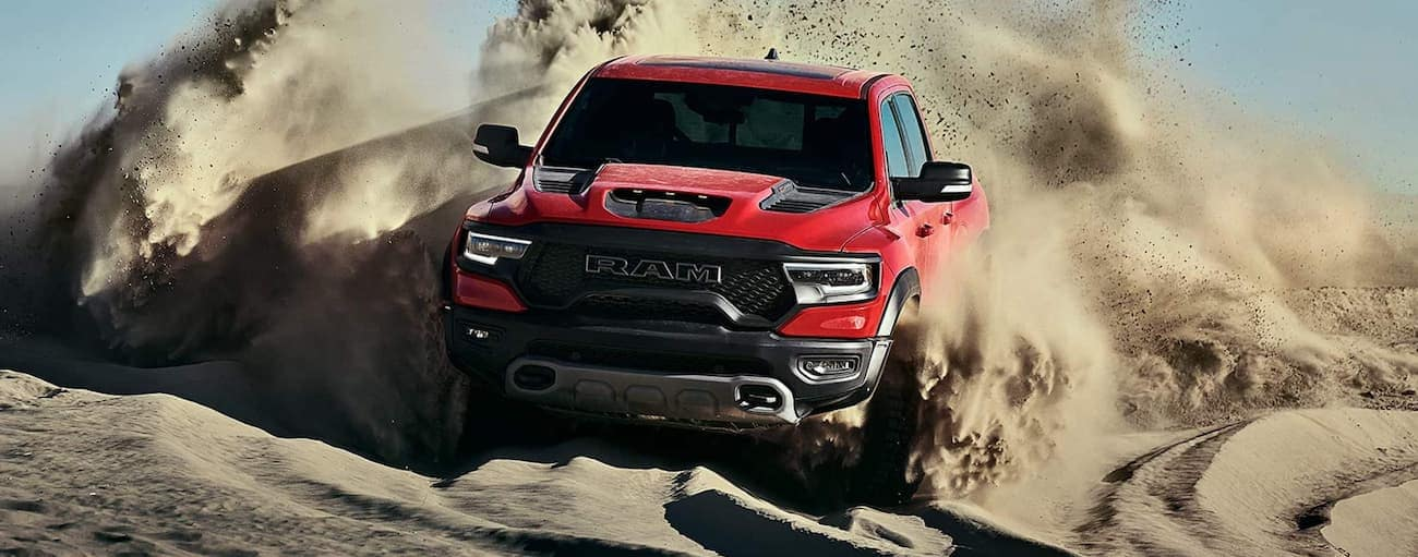 A red 2021 Ram 1500 TRX is off-roading on a sand dune.