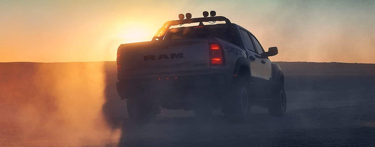 A silver 2021 Ram 1500 TRX is shown from the rear while off-roading at sunset near Lexington, KY.