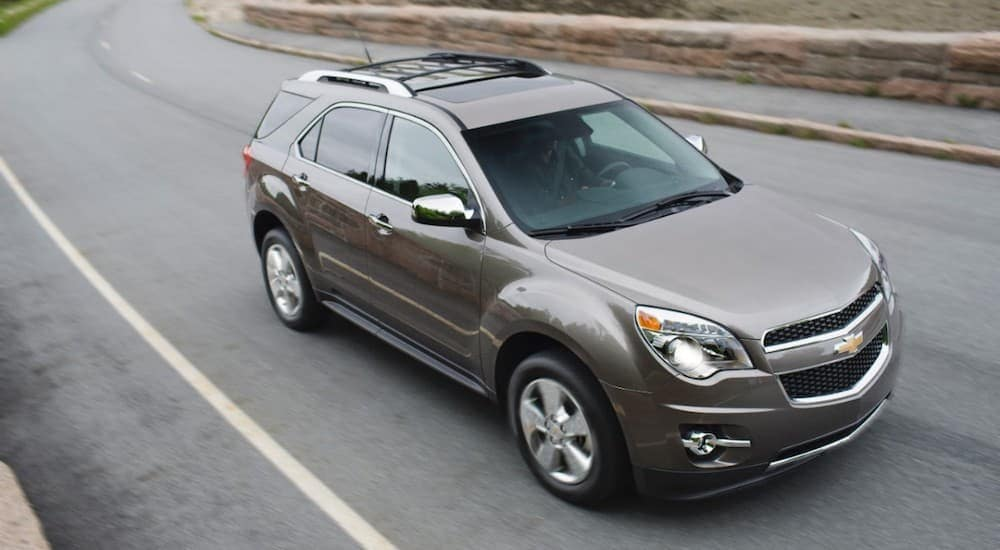 A grey 2012 Chevy Equinox is driving on a road past a stone wall near Lexington, KY.