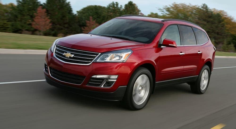 A red 2013 Chevy Traverse, which is popular among used cars near me, is driving on a highway past trees.