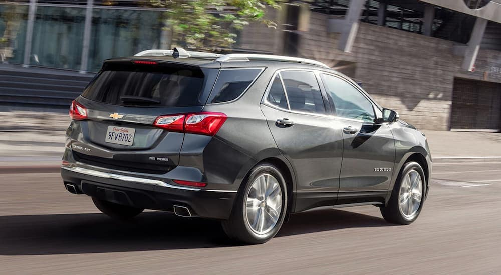 A grey 2020 Chevy Equinox is driving on a city street.