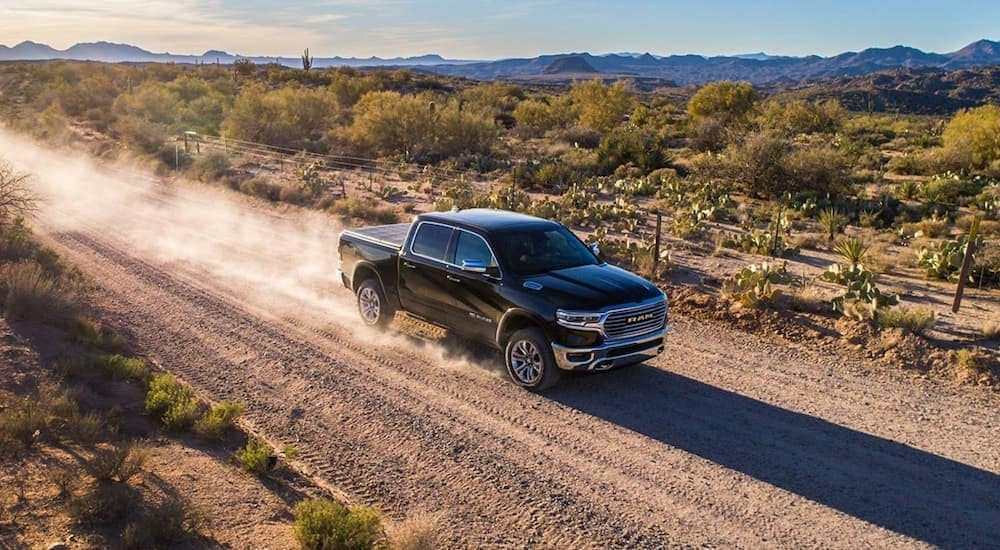 A black 2019 used Ram 1500 is driving on a dirt road in the desert.