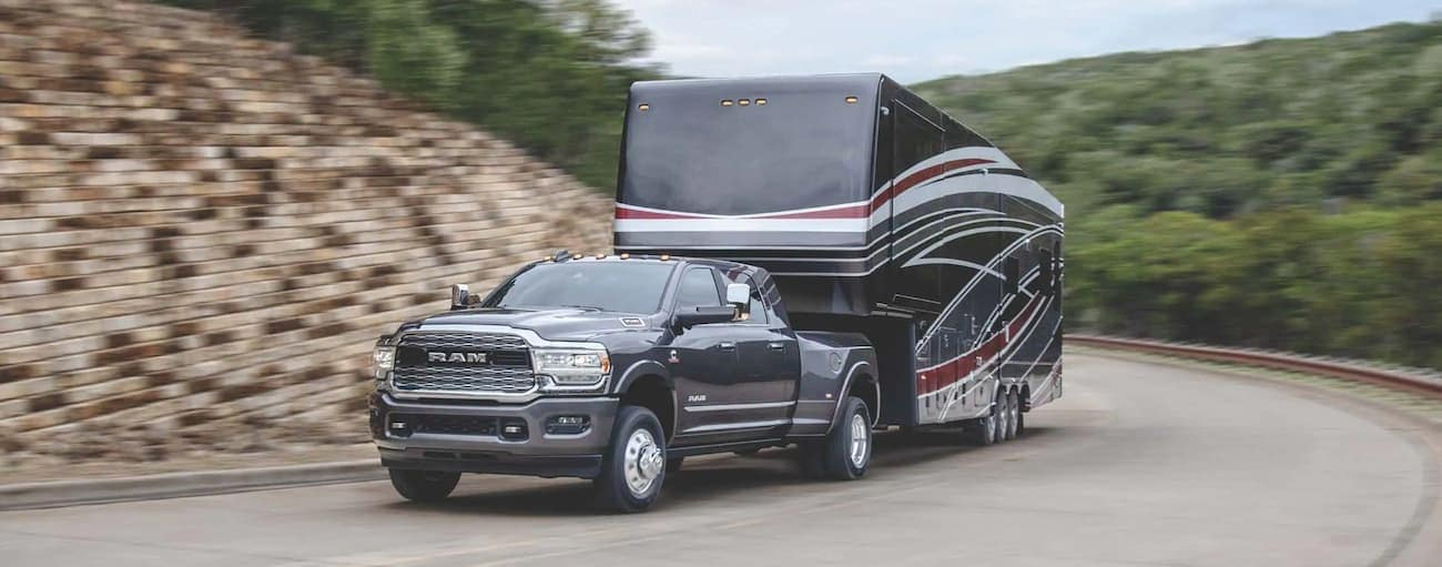 A grey 2020 Ram 3500 is towing a camper around a corner uphill.