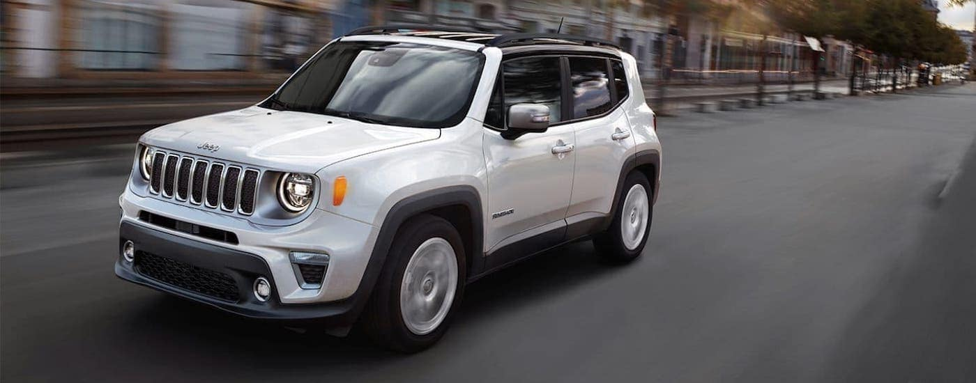 A white 2021 Jeep Renegade is driving on a city street.