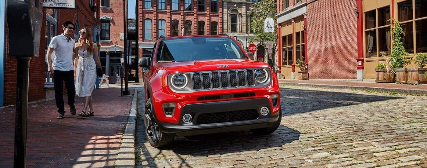 A couple is walking by a red 2021 Jeep Renegade that is parked on a cobblestone city street that is shown from the front.