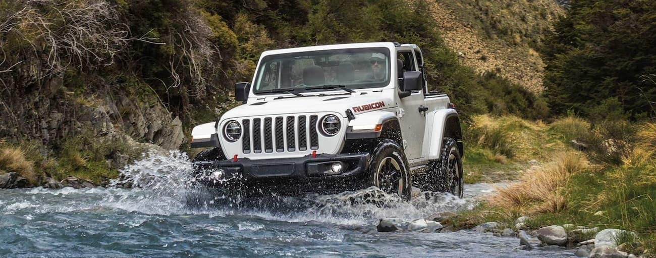 A white 2021 Jeep Wrangler Rubicon is crossing a river while off-roading.
