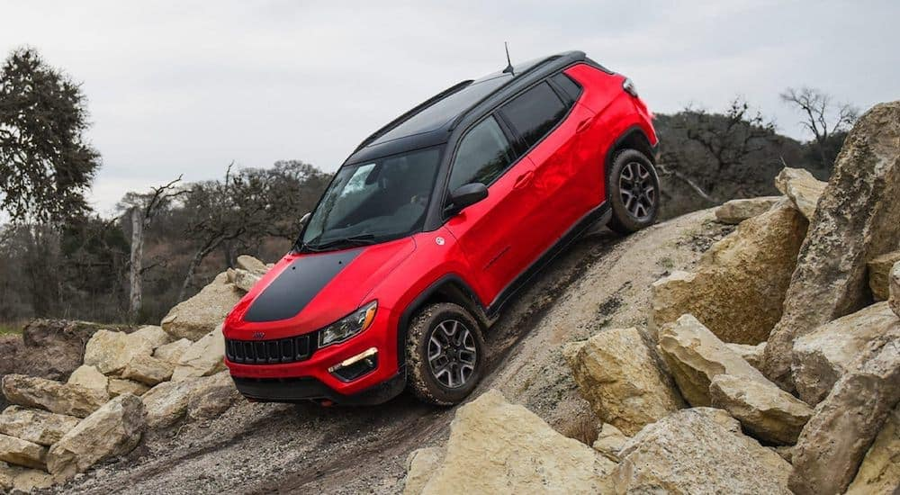 A red and black 2021 Jeep Compass is crawling down a rocky hill.