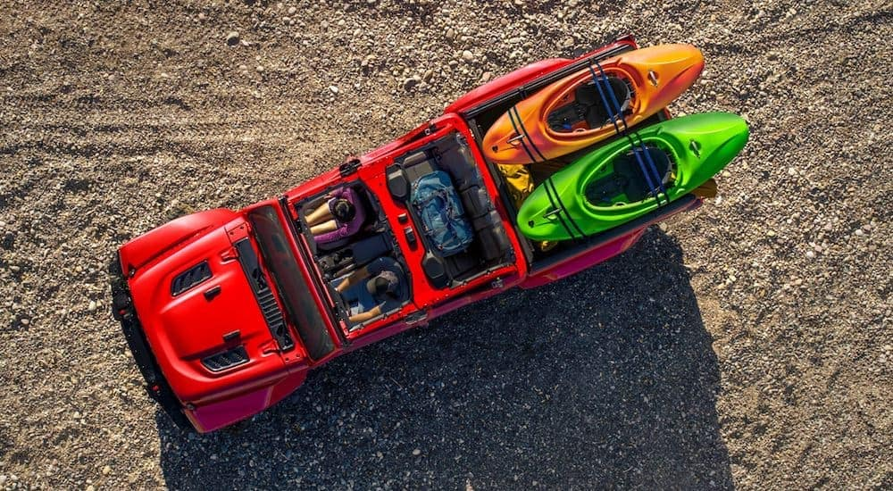A red 2021 Jeep Gladiator is shown from above with its top off and kayaks in the bed.