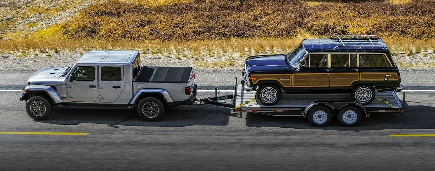 A silver 2021 Jeep Gladiator is shown from the side towing a vintage Jeep Grand Wagoneer on a rural road.