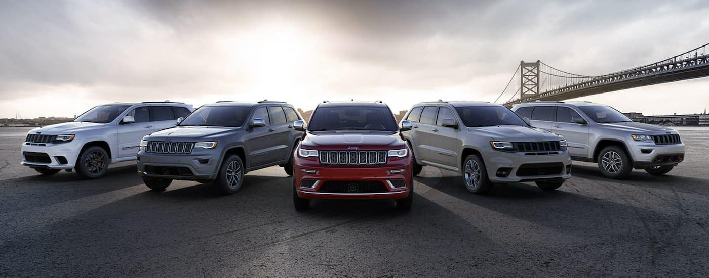 A line of five 2021 Jeep Grand Cherokees are shown in front of a city bridge.