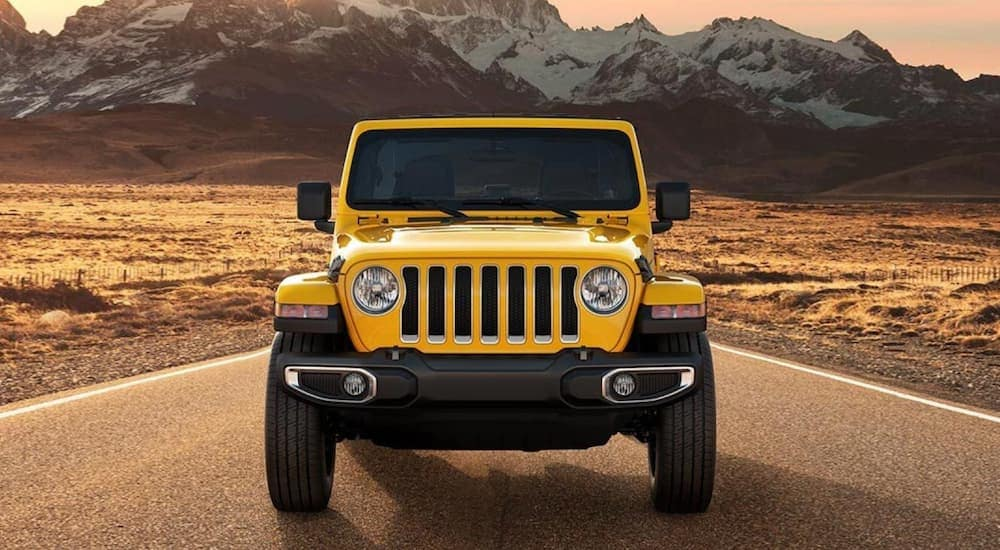 A yellow 2021 Jeep Wrangler from a a Jeep dealership near me is shown from the front while driving on a desert road with distant mountains.