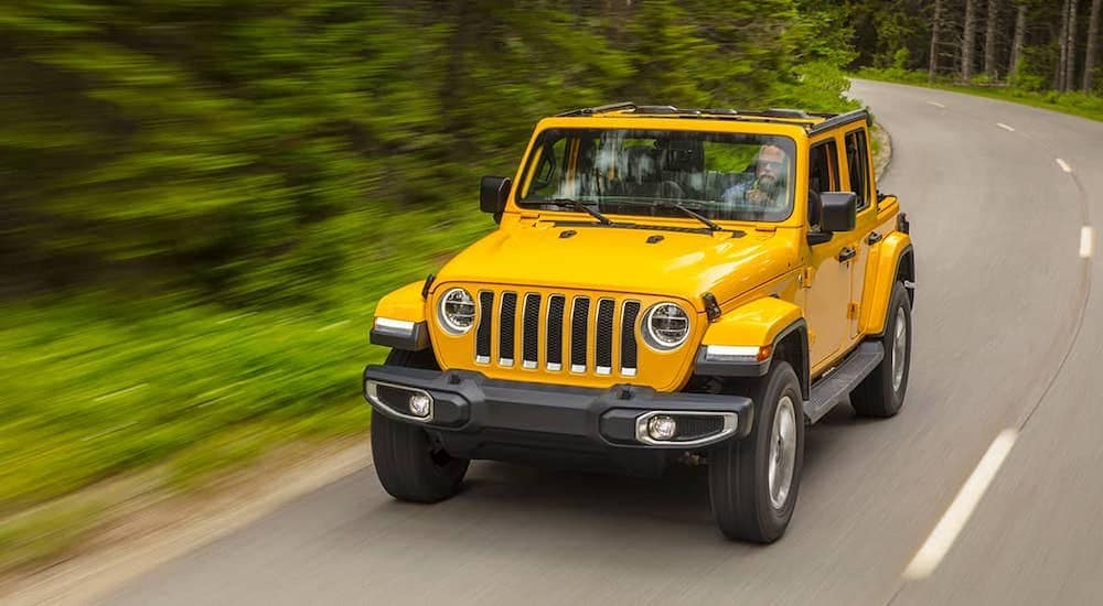 A yellow 2021 Jeep Wrangler is driving down the street past blurred trees after leaving a Jeep dealer near you.