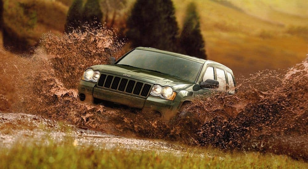A green 2011 used Jeep Grand Cherokee is driving through a mud puddle.