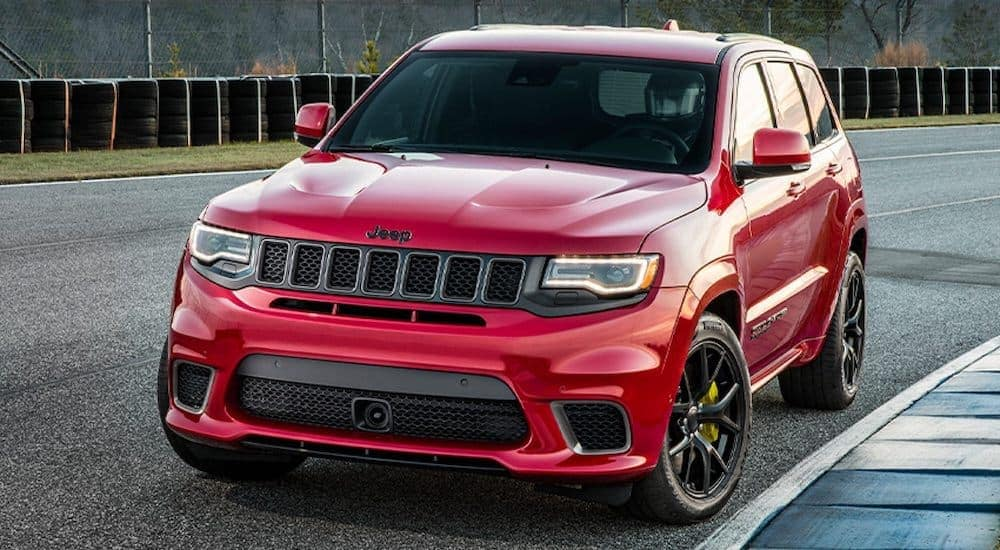 A red 2017 used Jeep Grand Cherokee Trackhawk is driving around the racetrack.