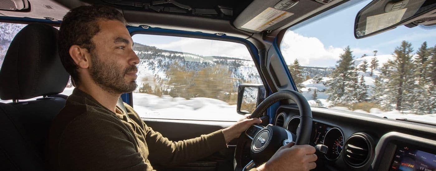 A man is driving a 2021 Jeep Gladiator and shown from the passenger side.