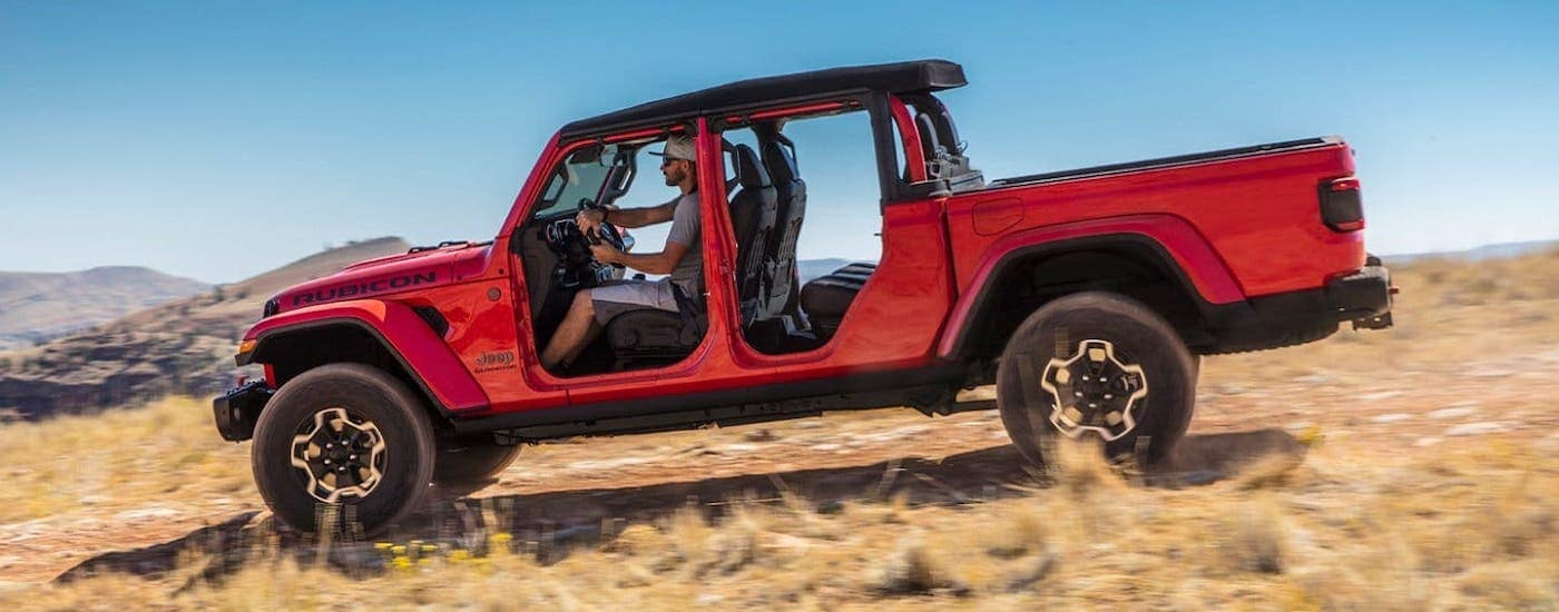 A red 2021 Jeep Gladiator Rubicon with no doors is driving in an empty field.
