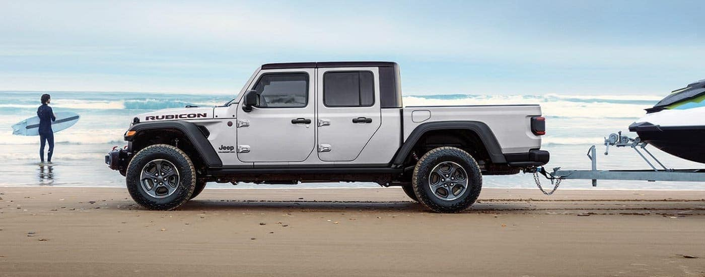 A silver 2021 Jeep Gladiator is towing a boat in front of a beach and surfer while shown from the side.