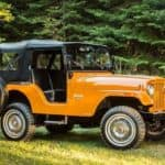 A orange 1955 Jeep CJ-5 is parked in the grass after leaving a Jeep Wrangler dealer near Lexington.