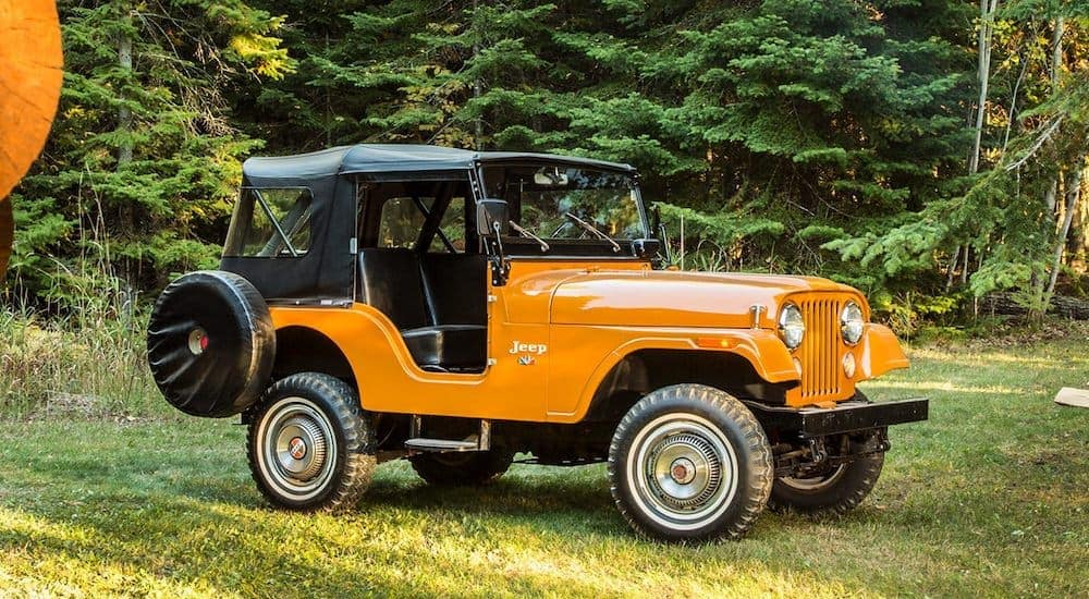 An orange 1955 Jeep CJ-5 is parked in the grass after leaving a Jeep Wrangler dealer near Lexington.