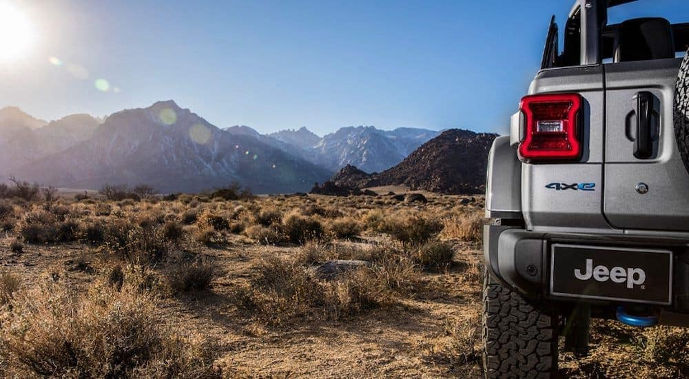 A grey 2021 Jeep Wrangler 4xe is shown from the rear in the desert with mountains in the distance.