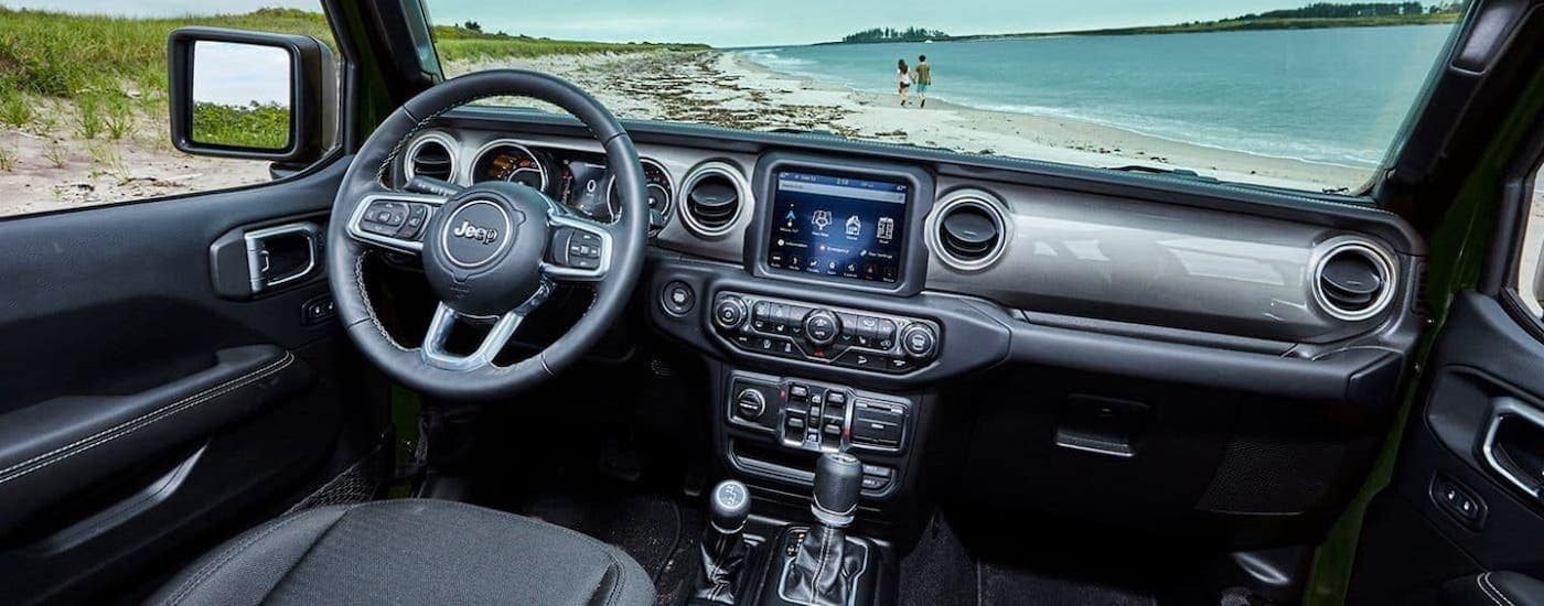 The dashboard and interior of a 2021 Jeep Wrangler is shown overlooking a beach.