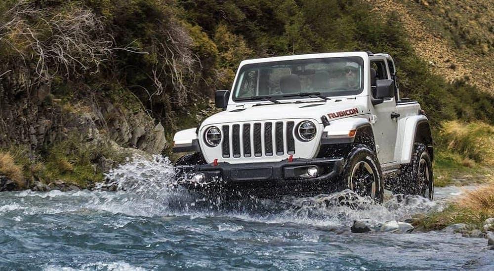 A white 2021 Jeep Wrangler Rubicon is driving through a river.