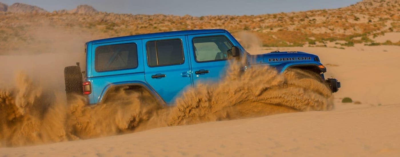 A blue 2021 Jeep Wrangler Rubicon Unlimited is kicking up sand in a dune after leaving a Jeep Wrangler Dealer near Lexington.