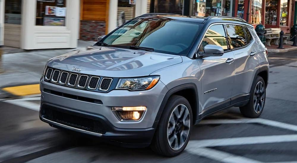 A silver 2020 Jeep Compass is driving on a city street after leaving a used Jeep dealer in Lexington.