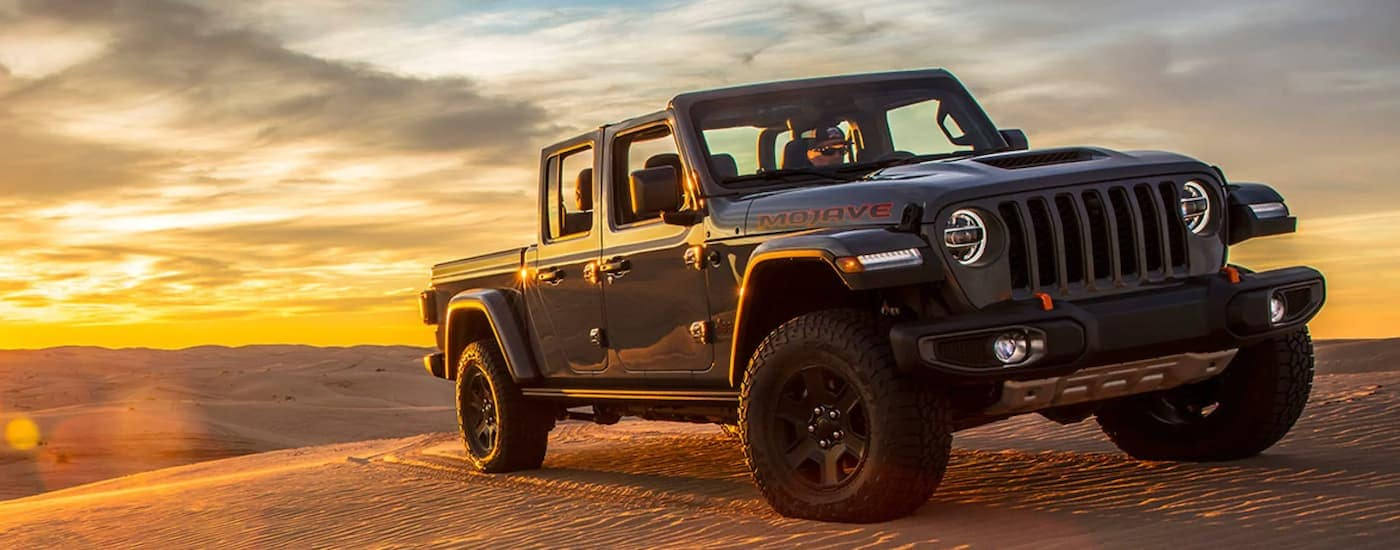 A dark grey 2020 Jeep Gladiator Mojave is off-roading in sand.
