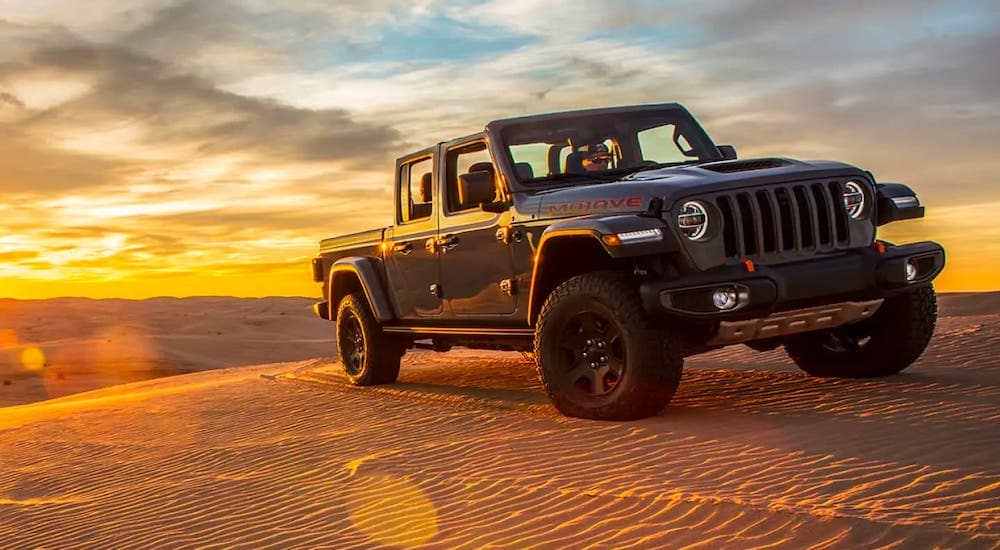 A gray 2020 used Jeep Gladiator Mojave with no roof is parked on sand dunes in front of a vibrant yellow sunset.
