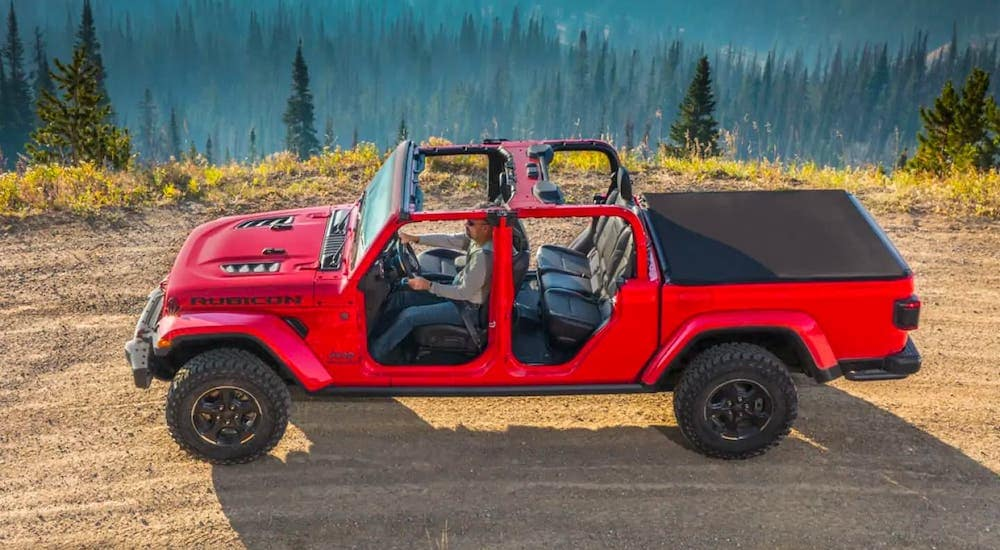 A red 2019 Jeep Gladiator with no roof or doors is shown from a high angle while driving on a mountain road.