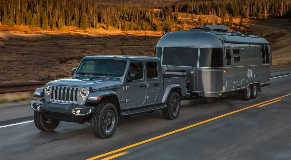 A silver 2019 used Jeep Gladiator is towing an Airstream trailer.