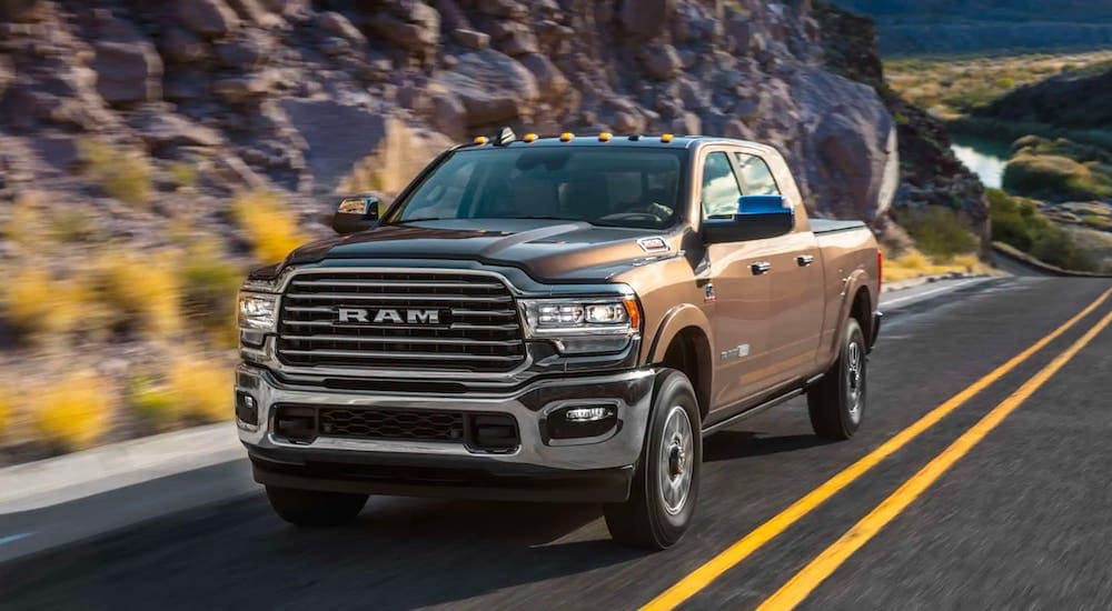A brown 2019 used Ram 2500 is driving on a rocky highway.