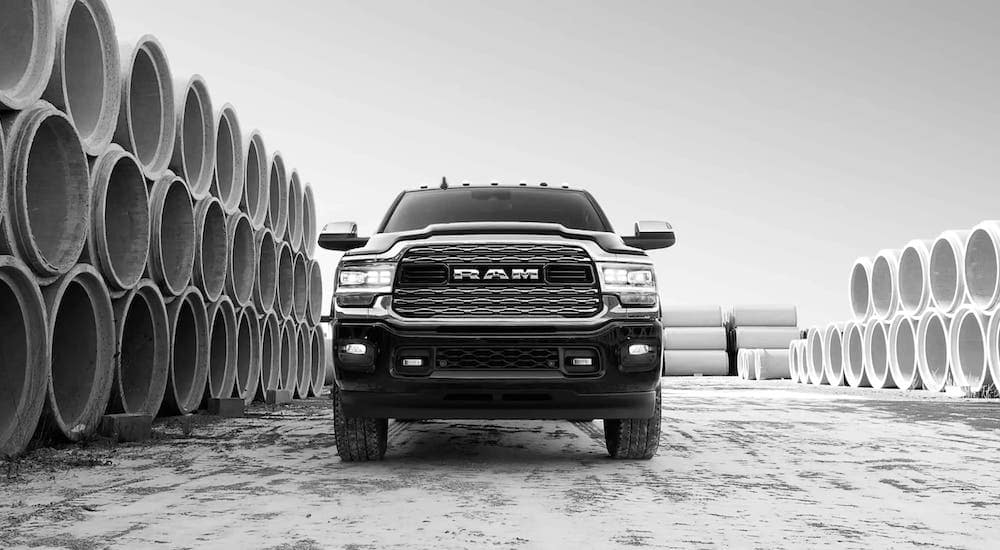 A black and white photo shows a black 2019 Ram 2500 surrounded by concrete pipes and shown from a low angle.