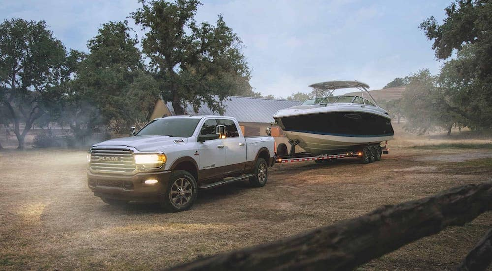 A white 2018 used Ram 2500 diesel is towing a boat at a ranch.