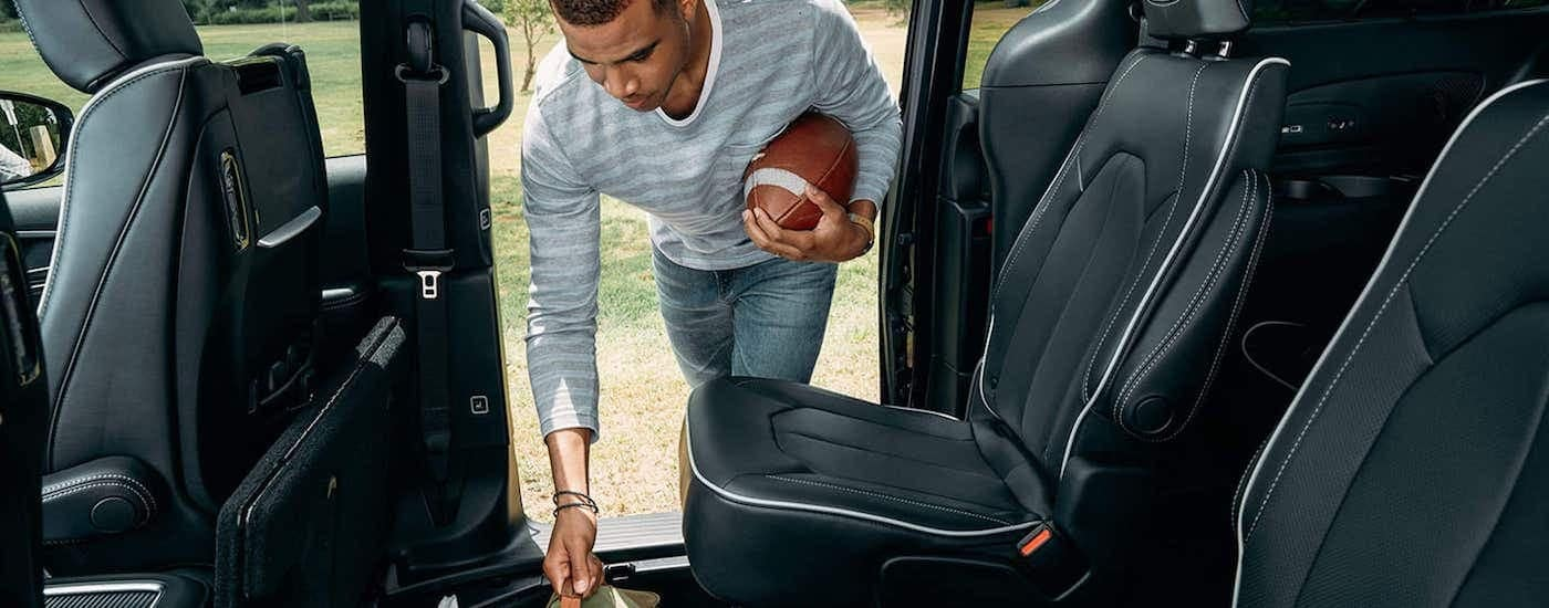 The black leather interior is shown with a man holding a football on a 2021 Chrysler Pacifica.
