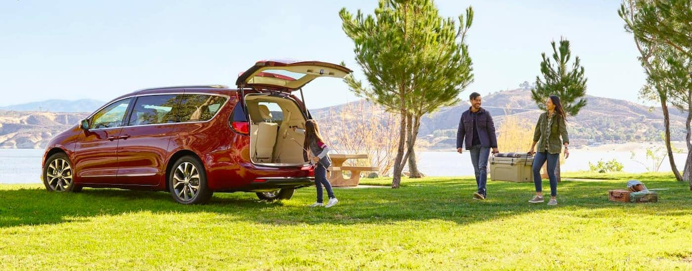 A red 2021 Chrysler Pacifica is shown parked in a field with a family packing after a picnic.