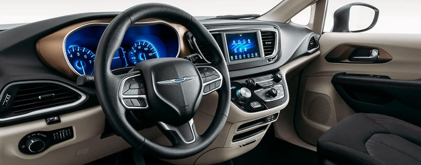 The tan and black interior is shown on a 2021 Chrysler Voyager.