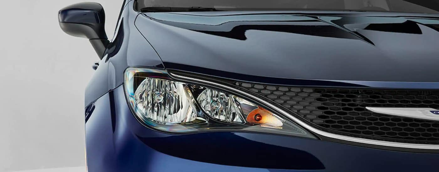 A close up is shown of the passenger headlight and grille on a 2021 Chrysler Voyager.