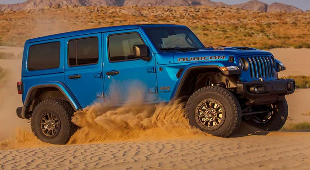 A blue 2021 Jeep Wrangler Rubicon 392 from a Lexington Jeep dealer is off-roading in the sand.