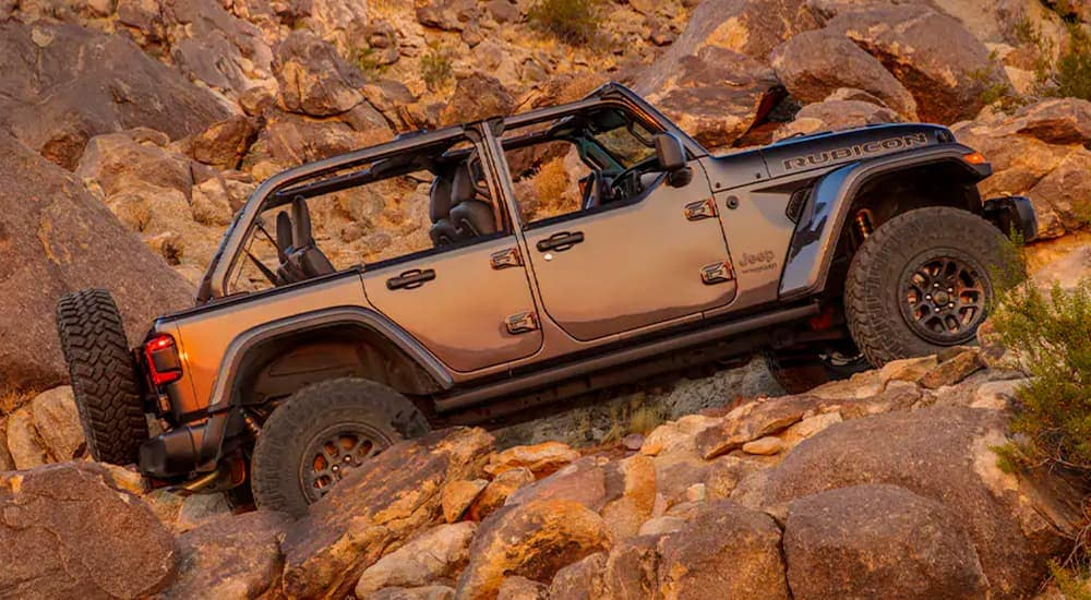 A grey 2021 Jeep Wrangler Rubicon 392 with no roof is off-roading on a rocky desert trail.