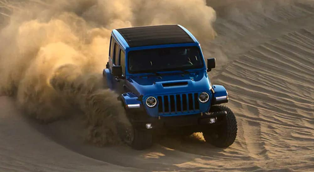 A blue 2021 Jeep Wrangler Rubicon 392 is off-roading on sand.